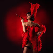Burlesque dancer with red plumage and short dress, black background — Stok fotoğraf