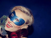 Smiling young blonde beauty with carnival masks — Stock Photo