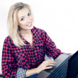 Cheerful young blonde girl using notebook. — Stock Photo