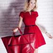 Beauty blonde girl posing in red dress, smiling. — Stock Photo