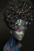 Painted mannequin girl with decorative headwear — Stock Photo