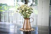 Flores blancas en una jarra de metal antigua en el cementoa de madera negra — Foto de Stock