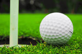 Golf ball on lip of cup — Stock Photo