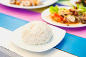 Rice in a white disc on colorful wood table — Stock Photo