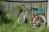Bicycle with basket on fence — Stock Photo