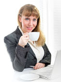 Businesswoman holding cup sitting at desk — Stock Photo