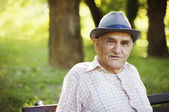 Senior man relaxing outdoors on a park early in the morning. — Stock Photo