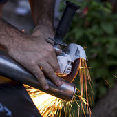 Man workin with iron, sparks — Stock Photo