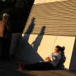 Mature couple relaxes during sunset on the roof of the Dockland Office Building. Hamburg. Dockland Office Building. June 2014. — Stock Photo #49373311