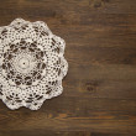 Crochet doily over dark wood — Stock Photo #39081543