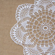 Crochet doily over burlap — Stock Photo
