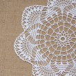 Crochet doily over burlap — Stock Photo #39082465