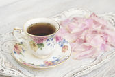Tea cup with peony petals — Stock Photo