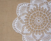 Crochet doily over burlap — Stock Photo