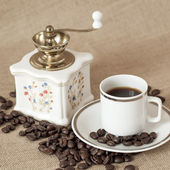 Antique coffee grinder and coffee cup — Stock Photo