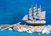 Toy sailboat, weathered wood and seashells on blue wood — Stok fotoğraf