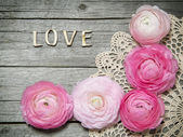 Ranunculus flowers and letters LOVE on wood — Stock Photo