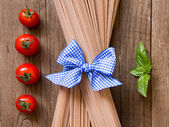 Pasta, tomatoes and basil on wooden background — Stock Photo