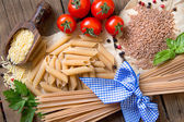Pasta, tomatoes, basil and parsley on wooden background — Stock Photo