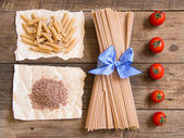 Pasta and  tomatoes on wooden background — Stock Photo
