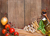 Pasta, tomatoes, onion, olive oil and basil on wooden background — Stock Photo