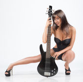 Sexy  girl with a guitar. In a black swimsuit, — Stock Photo