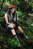 Girl with a rifle in the woods — Stock Photo