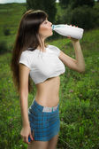 Girl in a t-shirt drinking milk. — Stock Photo