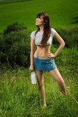 Meisje in een t-shirt consumptiemelk. — Stockfoto