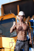 Muscular work on the background dump trucks — Stock Photo
