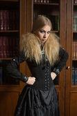Vintage sexy girl next to the bookcase, gothic — Stock fotografie