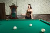 Sexy girl in corset plays billiards. — Stockfoto