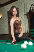 Sexy girl in corset plays billiards. — Stock Photo