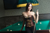 Sexy girl in corset plays billiards. — 图库照片