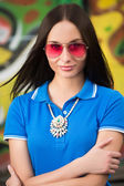 Sexy girl in pink glasses and a necklace — Stock Photo