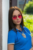 Girl in red glasses and blue shirt — Stock Photo