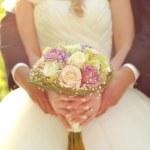 Wedding bouquet in hands of bride and groom — Stock Photo
