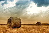 Hay bales in a field just before a storm — Stock Photo