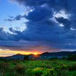 Colorful summer sunset just after a rainy day. Sun coloring the clouds. — Stock Photo #46718265