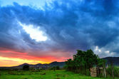 Colorful summer sunset just after a rainy day. Sun coloring the clouds. — Stock Photo