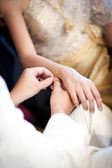 The groom wearing gold bracelet for his bride in wedding ceremony — Stock Photo