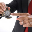 Businessmpointing to pocket watch — Stock Photo #39417513