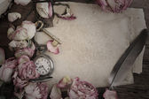 Taschenuhr von getrockneten Rosen und alten Papier auf Holz — Stockfoto