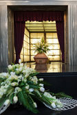 Wooden coffin with funeral flowers in crematorium — Stock Photo