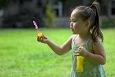 Girl in the summer yard blowing bubbles — Foto de Stock