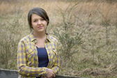 Country girl in flannel shirt by fence — Stock Photo