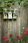 Flower garden birdhouses on a rustic fence — Stock Photo