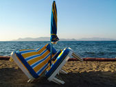 Sunbed and sunshade in front of the sea — Stock Photo
