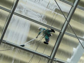 Man at work, pressure washing a glass roof — Stock Photo