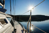 Sailing boat anchoring in calm water. sun reflection in water — Stock Photo